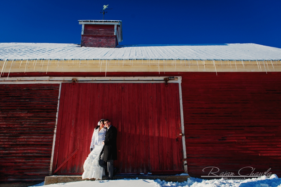 Photo of bride and groom in front of red barn in vermont.